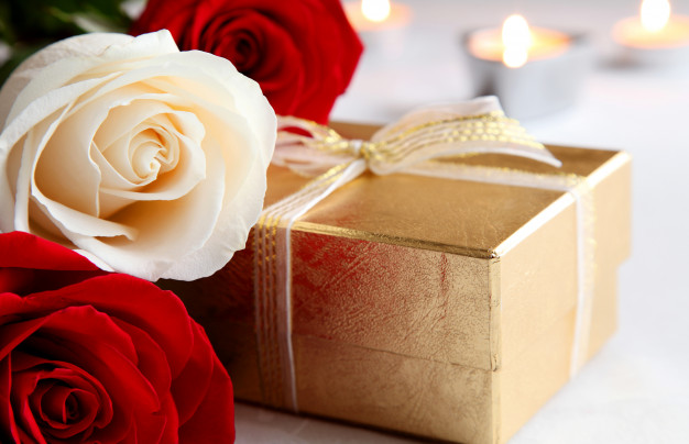 bouquet-roses-gift-background-burning-candles-valentine-s-day_138888-236