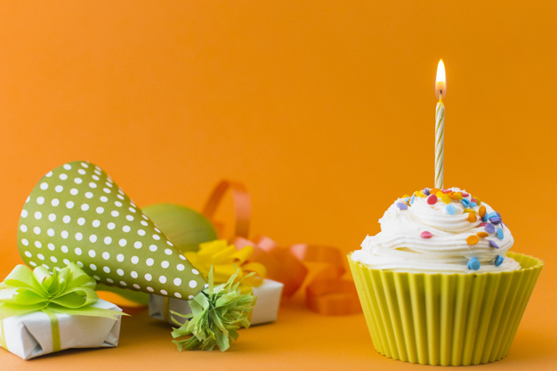 close-up-cupcake-near-gifts-part-hat-orange-background_23-2147917405
