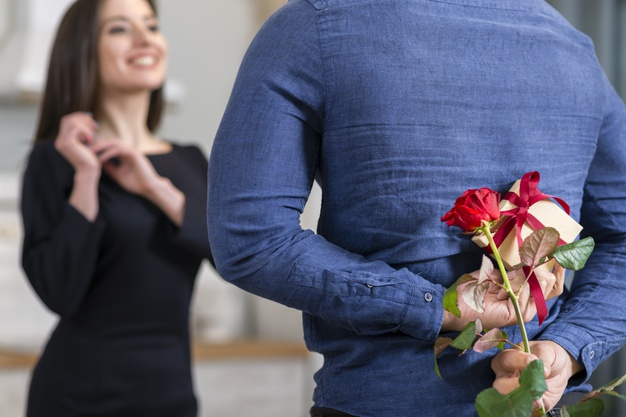 man-surprising-his-wife-with-valentine-s-day-gift-close-up_23-2148435868